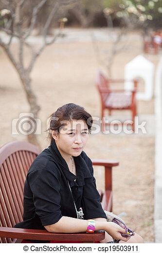 Asian women black shirt. Sitting on wooden bench. - csp19503911