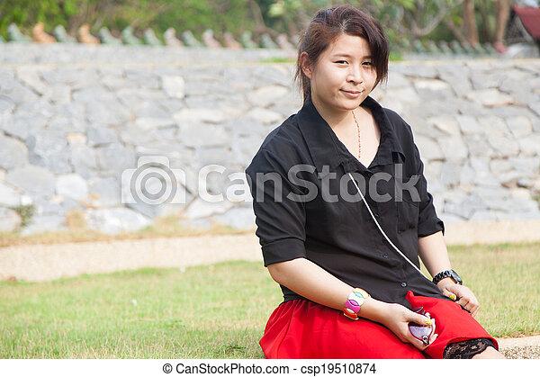 Asian women black shirt. Sitting on the lawn. - csp19510874