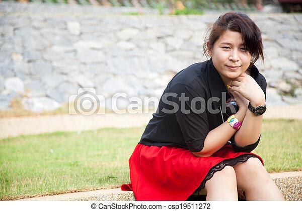 Asian women black shirt. Sitting on the lawn. - csp19511272