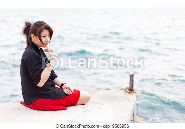 Asian women black shirt. Sitting on the sidewalk. - csp19506956
