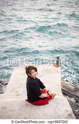 Asian women black shirt. Sitting on the sidewalk. - csp19507243
