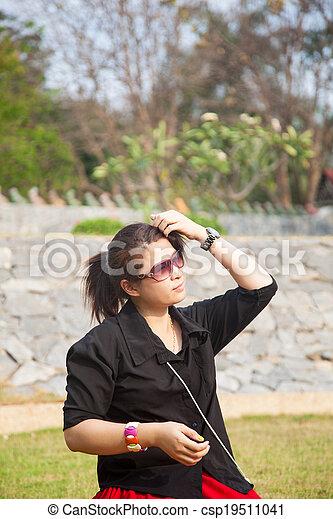 Asian women black shirt. Sitting on the lawn. - csp19511041