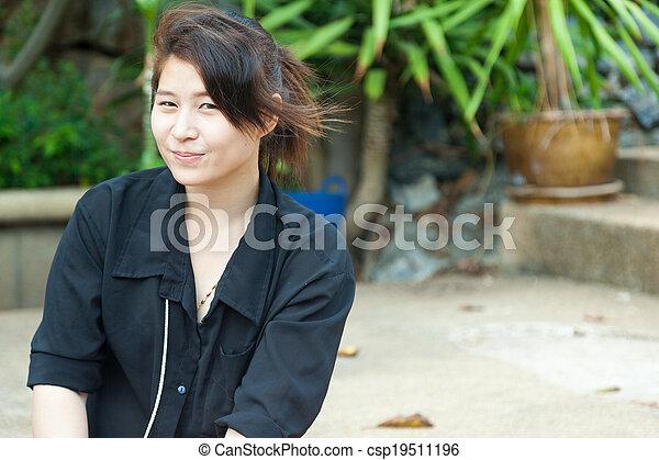 Asian women black shirt. Sitting on the lawn. - csp19511196
