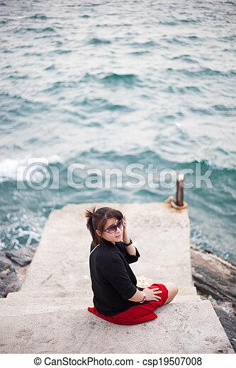 Asian women black shirt. Sitting on the sidewalk. - csp19507008