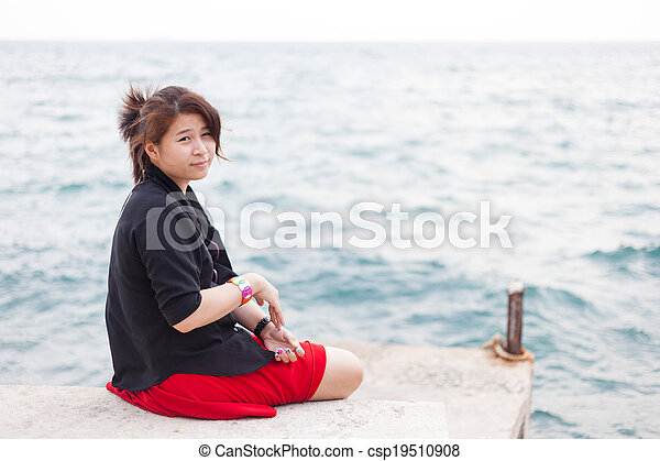 Asian women black shirt. Sitting on the sidewalk. - csp19510908