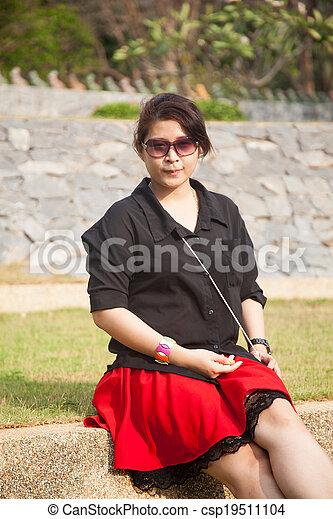 Asian women black shirt. Sitting on the lawn. - csp19511104