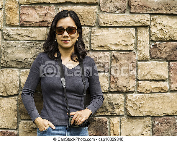 Asian Women Holding Camera Against Stone Wall Csp