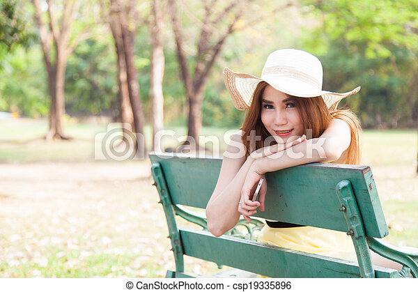 Asian women sitting on a bench in the park. - csp19335896
