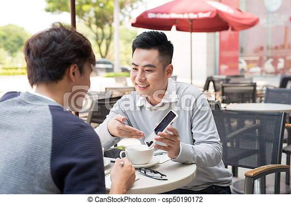 Asian young men enjoying watching on mobile phone together in cafe with coffee on the table. - csp50190172