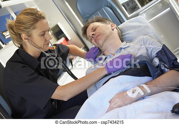 El paramédico atiende al paciente en ambulancia - csp7434215