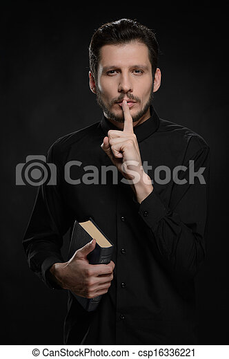 Asking to keep silence. Portrait of priest holding his hand against lips while standing against black background - csp16336221