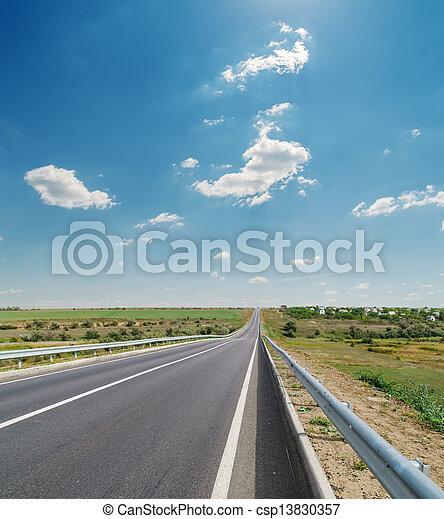 asphalt road closeup under cloudy blue sky - csp13830357