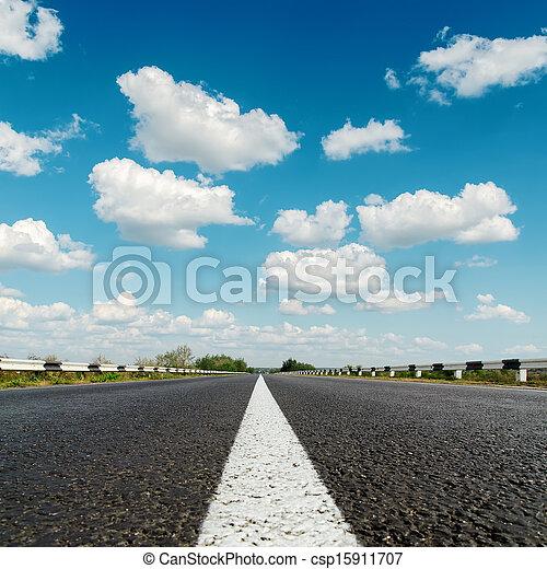 asphalt road under blue cloudy sky - csp15911707