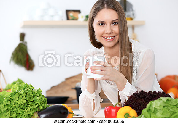 assento mulher, madeira, legumes, copo, olhando jovem, enquanto, câmera, verde, segurando, tabela, branca, feliz, cozinha - csp48035656