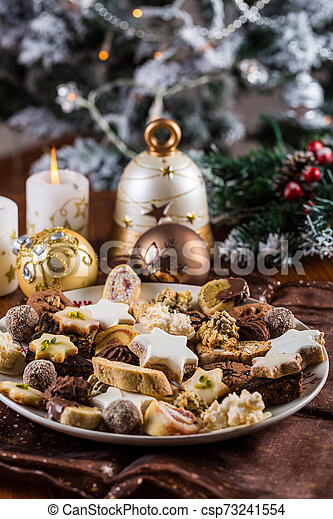 Assorted Christmas cookies with candles on the table - csp73241554