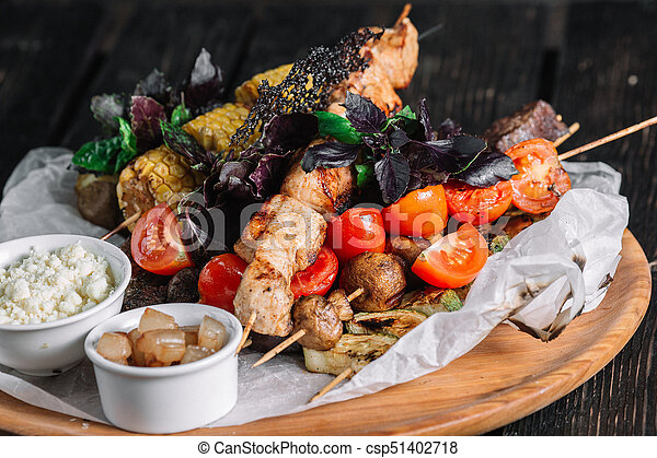 Assorted delicious grilled meat with vegetable served with cracklings and brynza on a wooden board on dark wood background - csp51402718