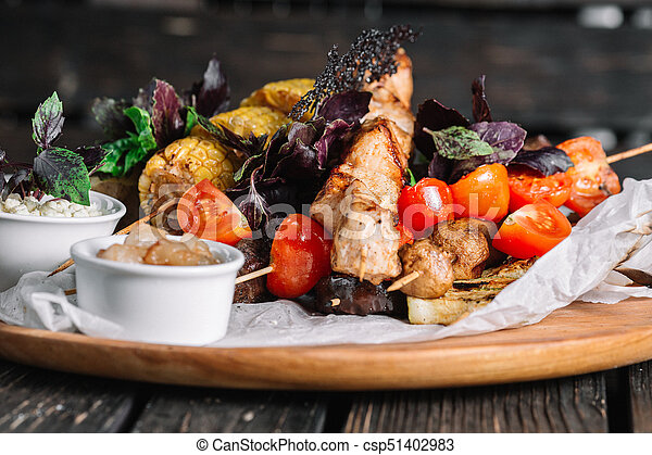 Assorted delicious grilled meat with vegetable served with cracklings and brynza on a wooden board on dark wood background - csp51402983