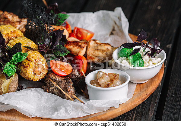 Assorted delicious grilled meat with vegetable served with cracklings and brynza on a wooden board on dark wood background - csp51402850