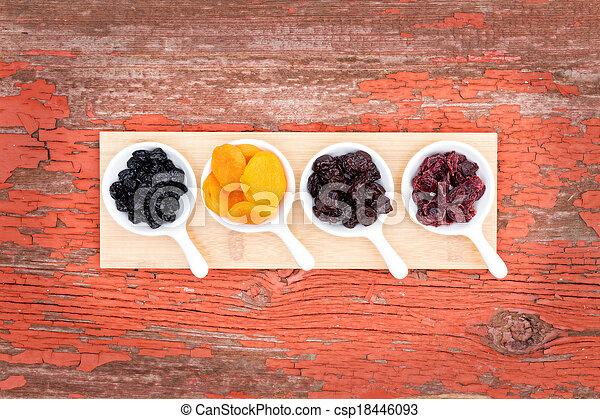 Assorted dried berries and fruit in ramekins - csp18446093