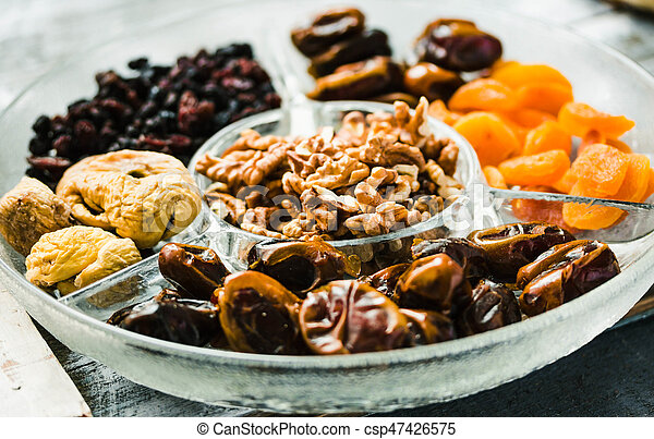 Assorted dried fruits and nuts on a glass plate - csp47426575
