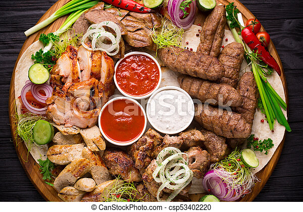 Assorted grilled meat and vegetables on rustic table - csp53402220