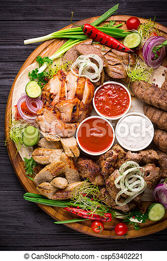 Assorted grilled meat and vegetables on rustic table - csp53402221