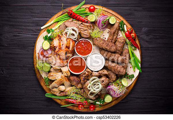 Assorted grilled meat and vegetables on rustic table - csp53402226