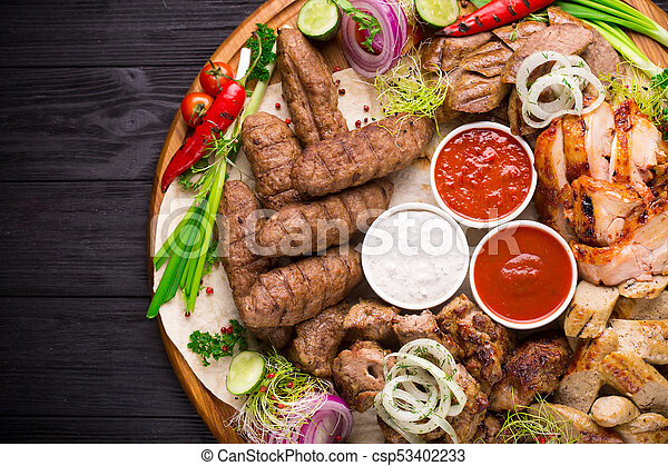 Assorted grilled meat and vegetables on rustic table - csp53402233