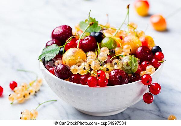 Assortment of fresh berries in white bowl - csp54997584