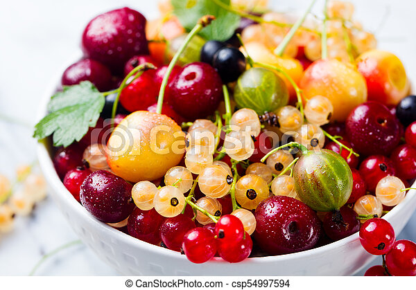 Assortment of fresh berries in white bowl. - csp54997594