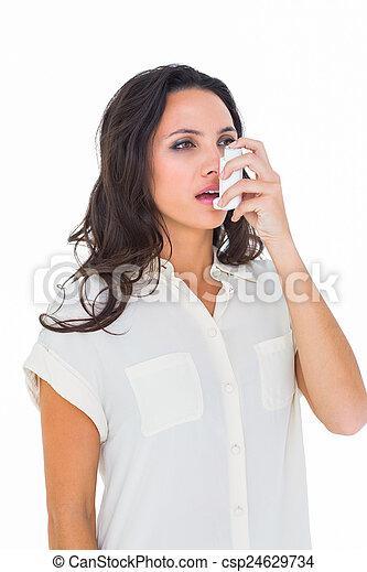 Asthmatic brunette using her inhaler  - csp24629734