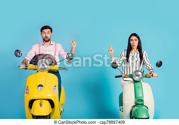 Astonished two people wife husband bikers ride yellow green motor bike impressed ads look on journey point index finger copyspace wear striped pink shirt isolated blue color background - csp78897409