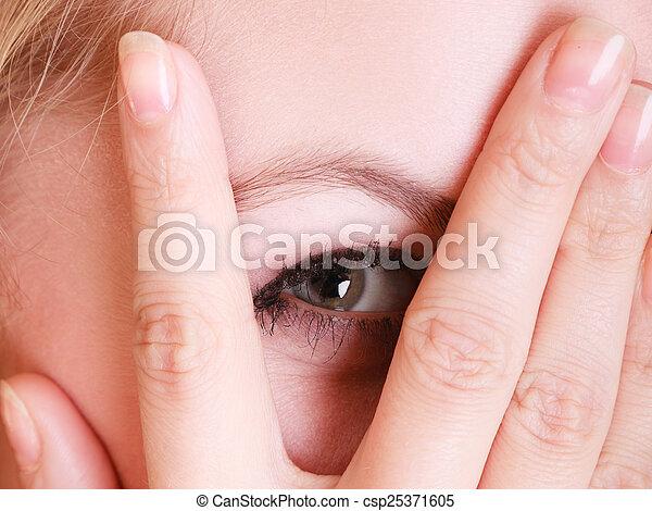 Una tímida mujer asustada mirando a través de los dedos - csp25371605