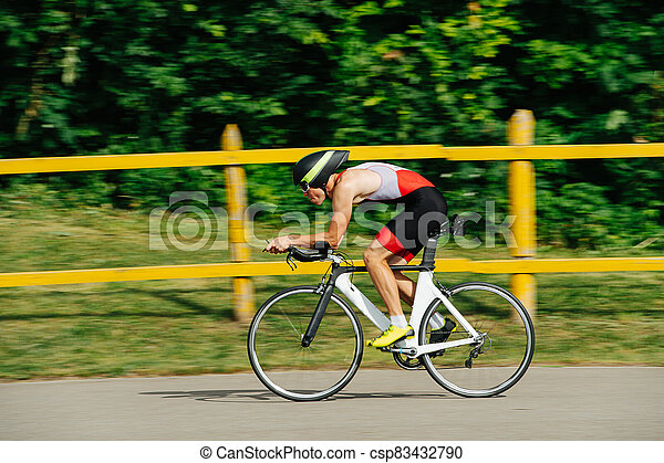 Athlete in low posture riding on a pro bike with streamlined helmet. Side view. - csp83432790