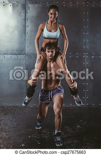 Athlete muscular sportsman doing exercising squats with woman sitting on his shoulders Crossfit fitness sport training lifestyle bodybuilding concept. - csp27675663