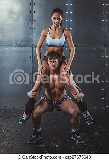 Athlete muscular sportsman doing exercising squats with woman sitting on his shoulders Crossfit fitness sport training lifestyle bodybuilding concept. - csp27675640