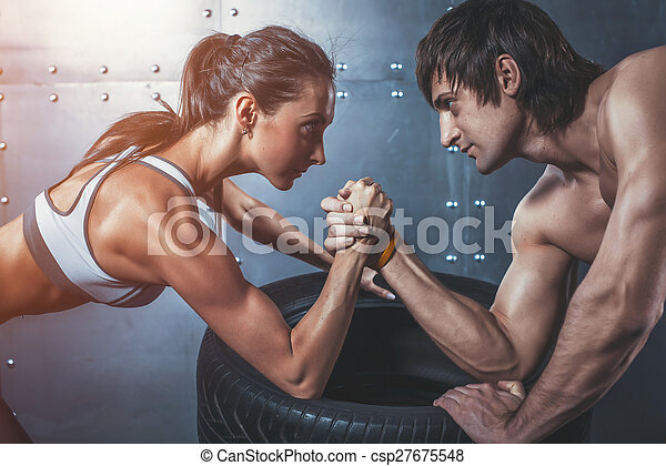 Athlete muscular sportsmen man and woman with hands clasped arm wrestling challenge between a young couple Crossfit fitness sport training lifestyle bodybuilding concept. - csp27675548