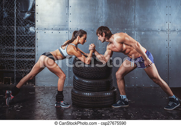 Athlete muscular sportsmen man and woman with hands clasped arm wrestling challenge between a young couple Crossfit fitness sport training lifestyle bodybuilding concept. - csp27675590