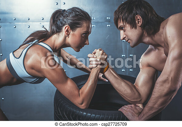 Athlete muscular sportsmen man and woman with hands clasped arm wrestling challenge between a young couple Crossfit fitness sport training lifestyle bodybuilding concept. - csp27725709