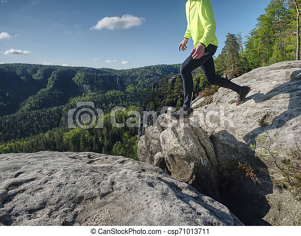 Athlete while jumping during a trail running in the mountains - csp71013711