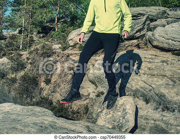 Athlete while jumping during a trail running in the mountains - csp70449355