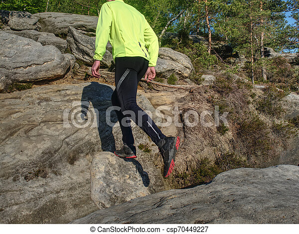 Athlete while jumping during a trail running in the mountains - csp70449227