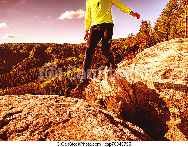 Athlete while jumping during a trail running in the mountains - csp70049735