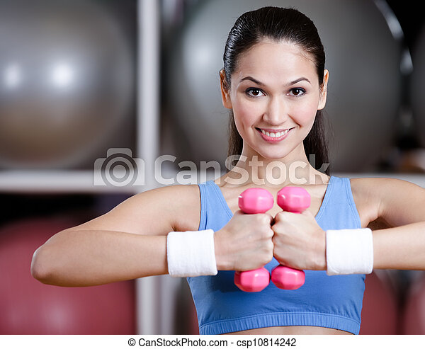 Athlete woman training with dumbbells - csp10814242