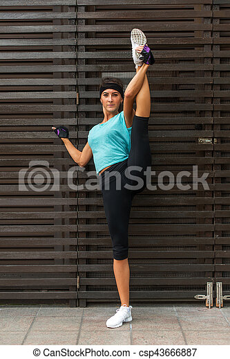 athletic flexible young woman doing standing split