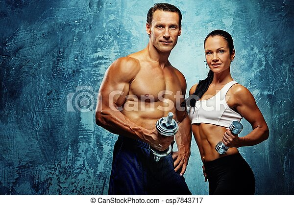 Athletic man and woman with a dumbells. - csp7843717