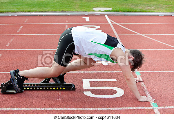 athletic man on the starting line putting his foot in the starting block  in a stadium  - csp4611684