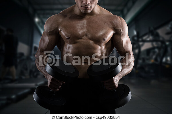 Athletic man training biceps at the gym - csp49032854
