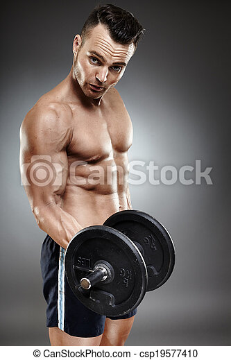 Athletic man working out with dumbbells - csp19577410