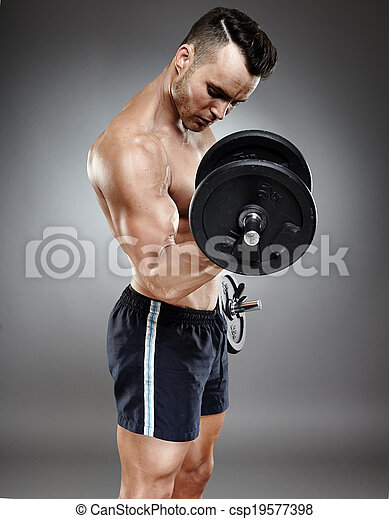 Athletic man working out with dumbbells - csp19577398